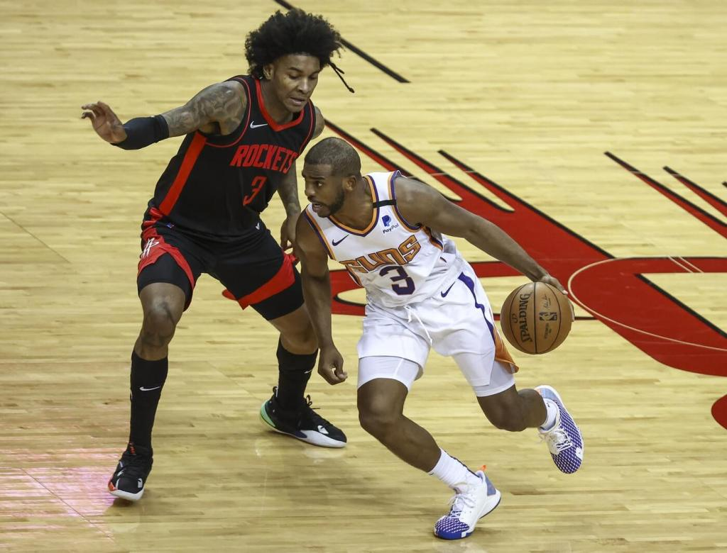Apr 5, 2021; Houston, Texas, USA; Positive Record Phoenix Suns guard Chris Paul (right) dribbles the ball against Houston Rockets guard Kevin Porter Jr. (left) during the third quarter at Toyota Center. Mandatory Credit: Troy Taormina-USA TODAY Sports