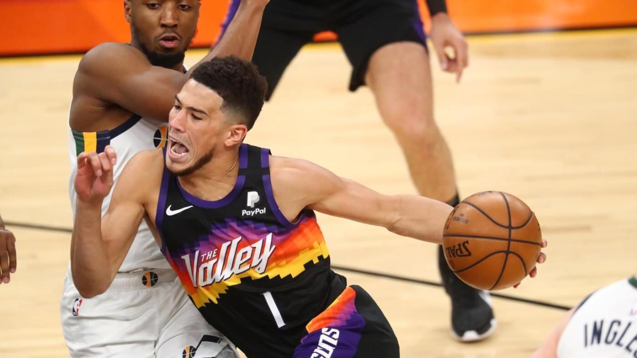 Apr 7, 2021; Phoenix, Arizona, USA; Phoenix Suns guard Devin Booker (1) reacts as he drives to the basket against Utah Jazz guard Donovan Mitchell during the first half at Phoenix Suns Arena. Mandatory Credit: Mark J. Rebilas-USA TODAY Sports