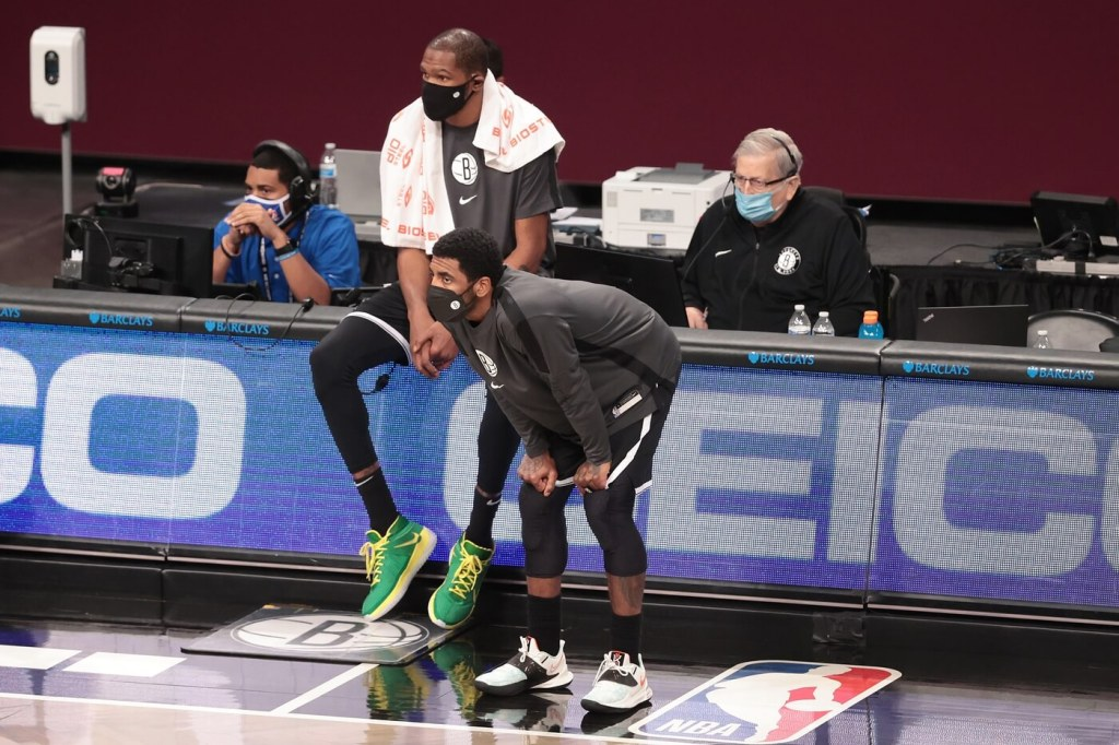 Jan 23, 2021; Brooklyn, New York, USA; Brooklyn Nets forward Kevin Durant (sitting) and guard Kyrie Irving (foreground) look on during the first half against the Miami Heat at Barclays Center. Mandatory Credit: Vincent Carchietta-USA TODAY Sports