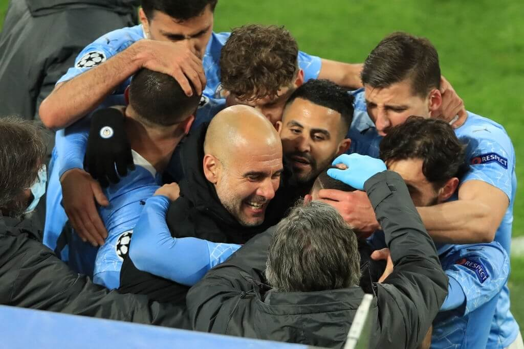 TOPSHOT - Manchester City's English midfielder Phil Foden (C, hidden) celebrates scoring the 1-2 goal with his team-mates and Manchester City's Spanish manager Pep Guardiola during the UEFA Champions League quarter-final second leg football match between BVB Borussia Dortmund and Manchester City in Dortmund, western Germany, on April 14, 2021.