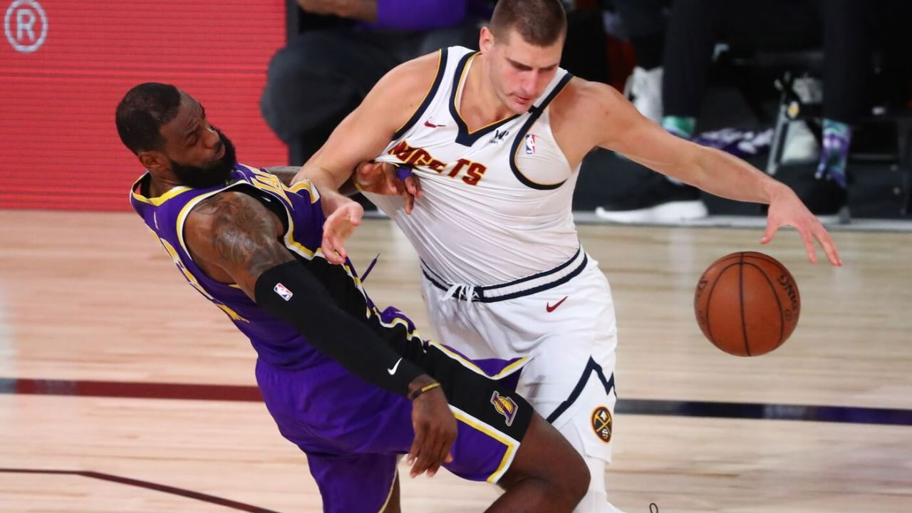 Sep 26, 2020; Lake Buena Vista, Florida, USA; Denver Nuggets center Nikola Jokic (15) is fouled by Los Angeles Lakers forward LeBron James (23) during the third quarter in game five of the Western Conference Finals of the 2020 NBA Playoffs at AdventHealth Arena.