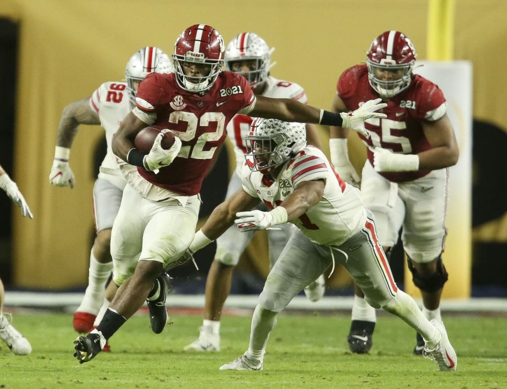 Alabama Crimson Tide running back Najee Harris (22) breaks away from Ohio State linebacker Justin Hilliard (47) as he runs during the College Football Playoff National Championship Game in Hard Rock Stadium.