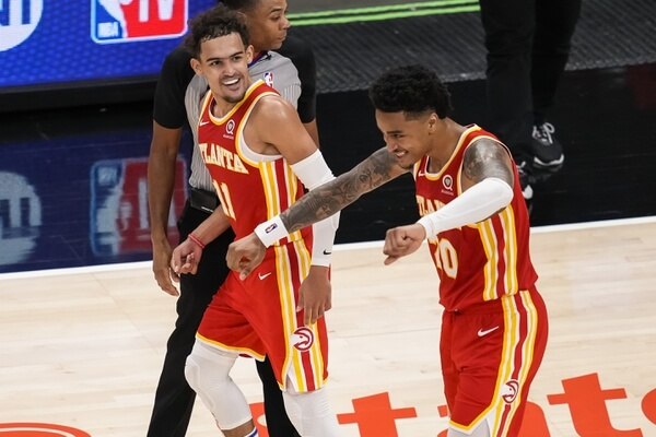 May 12, 2021; Atlanta, Georgia, USA; Atlanta Hawks forward John Collins (20) reacts with guard Trae Young (11) after making a three point shot in the last minute to give the Hawks the lead over the Washington Wizards during the second half at State Farm Arena. Mandatory Credit: Dale Zanine-USA TODAY Sports
