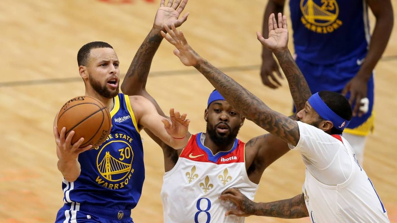 May 4, 2021; New Orleans, Louisiana, USA; Golden State Warriors guard Stephen Curry (30) drives on New Orleans Pelicans forwards Naji Marshall (8) and James Johnson (16) in the second quarter at the Smoothie King Center. Mandatory Credit: Chuck Cook-USA TODAY Sports