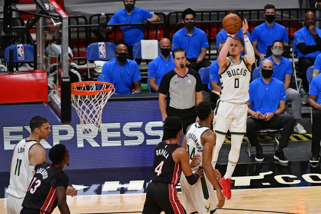 Dec 29, 2020; Miami, Florida, USA; Milwaukee Bucks guard Donte DiVincenzo (0) attempts a three point shot against the Miami Heat during the second half at American Airlines Arena. Mandatory Credit: Jasen Vinlove-USA TODAY Sports