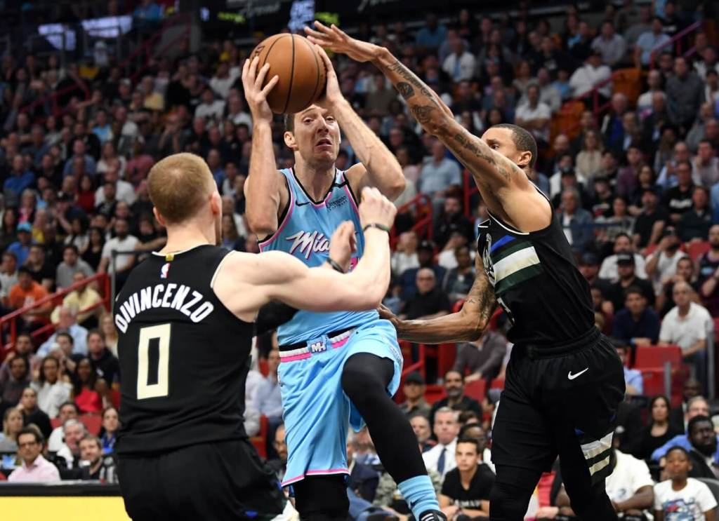 Mar 2, 2020; Miami, Florida, USA; Miami Heat guard Goran Dragic (7) drives to the basket between Milwaukee Bucks guard George Hill (3) and guard Donte DiVincenzo (0) in the fourth quarter at American Airlines Arena. Mandatory Credit: Jim Rassol-USA TODAY Sports