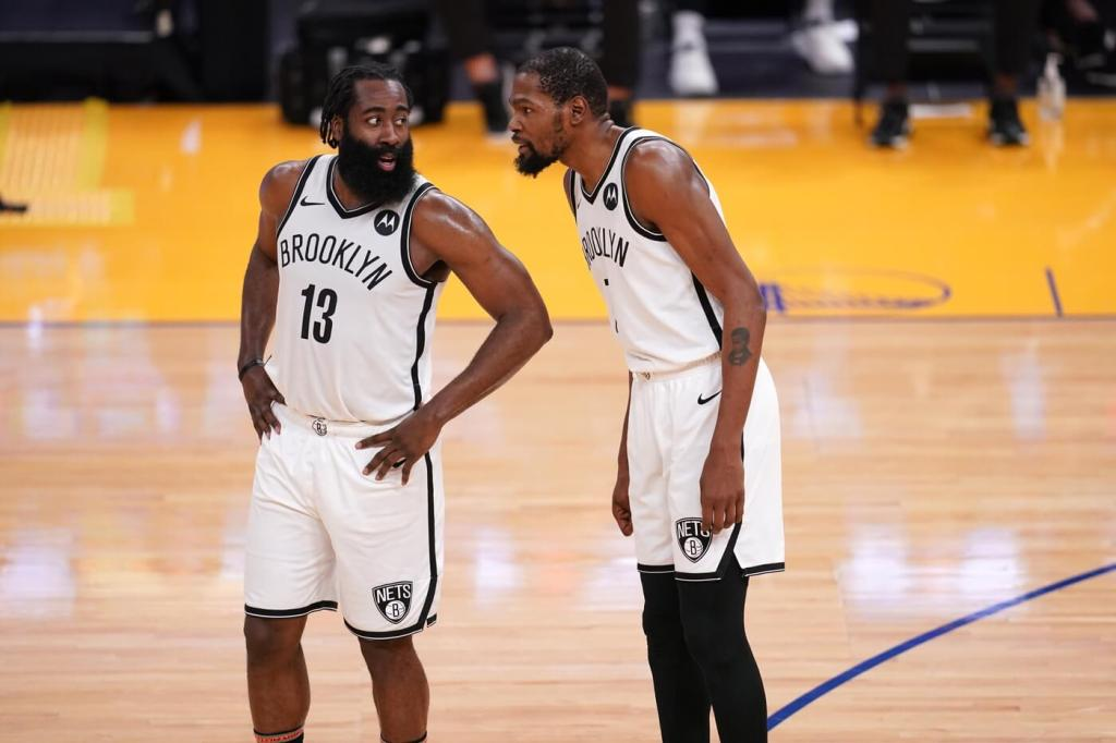 Feb 13, 2021; San Francisco, California, USA; Brooklyn Nets guard James Harden (13) talks with forward Kevin Durant (7) during a free throw attempt by the Nets against the Golden State Warriors in the third quarter at the Chase Center. Mandatory Credit: Cary Edmondson-USA TODAY Sports