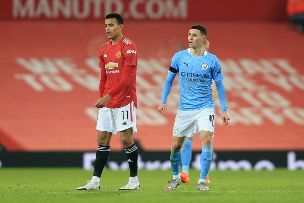 MANCHESTER, ENGLAND - JANUARY 06: Mason Greenwood of Man Utd and Phil Foden of Manchester City during the Carabao Cup Semi Final match between Manchester United and Manchester City at Old Trafford on January 6, 2021 in Manchester, England.