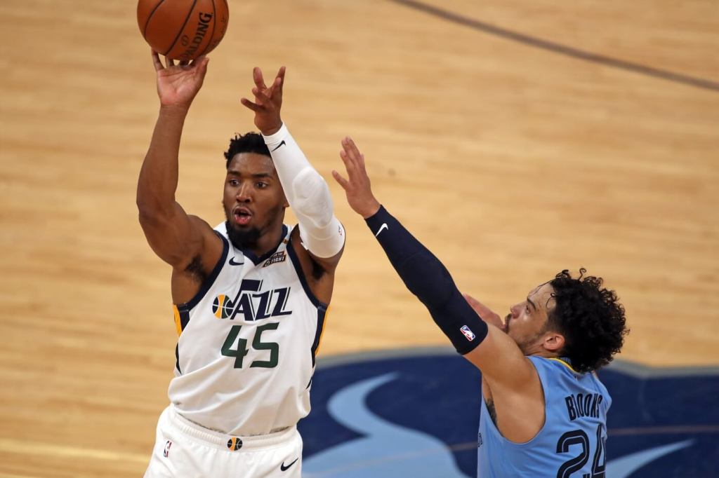 May 29, 2021; Memphis, Tennessee, USA; Utah Jazz guard Donovan Mitchell (45) shoots for three over Memphis Grizzlies forward Dillon Brooks (24) during the fourth quarter during game three in the first round of the 2021 NBA Playoffs at FedExForum. Mandatory Credit: Petre Thomas-USA TODAY Sports