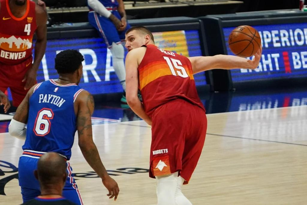 May 5, 2021; Denver, Colorado, USA;Denver Nuggets center Nikola Jokic (15) shoots from behind his back over New York Knicks guard Elfrid Payton (6) in the first quarter at Ball Arena. Mandatory Credit: Ron Chenoy-USA TODAY Sports