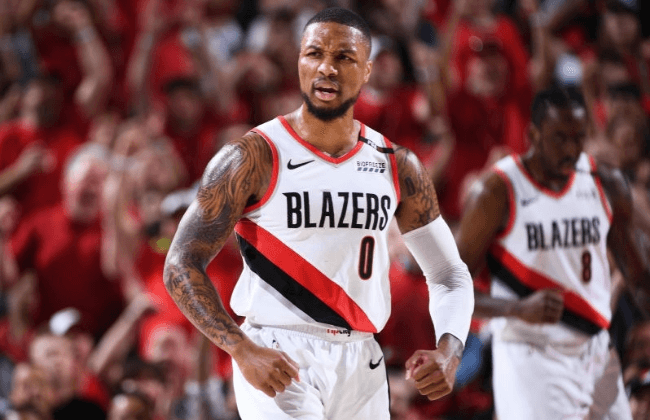 PORTLAND, OR - MAY 5: Damian Lillard #0 of the Portland Trail Blazers reacts during a game against the Denver Nuggets during Game Four of the Western Conference Semifinals on May 5, 2019 at the Moda Center Arena in Portland, Oregon. NOTE TO USER: User expressly acknowledges and agrees that, by downloading and or using this photograph, user is consenting to the terms and conditions of the Getty Images License Agreement. Mandatory Copyright Notice: Copyright 2019 NBAE (Photo by Garrett Ellwood/NBAE via Getty Images)