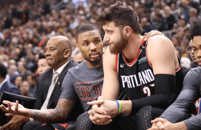 Mar 1, 2019; Toronto, Ontario, CAN; Portland Trail Blazers point guard Damian Lillard (0) talks to center Jusuf Nurkic (27) on the bench against the Toronto Raptors at Scotiabank Arena. The Raptors beat the Trail Blazers 119-117