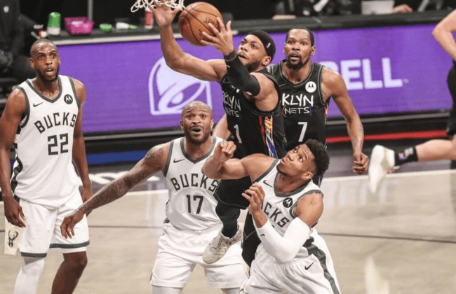 Jun 7, 2021; Brooklyn, New York, USA; Brooklyn Nets guard Bruce Brown (1) jumps over Milwaukee Bucks forwards P.J. Tucker (17) and Giannis Antetokounmpo (34) to grab a rebound in the third quarter during game two in the second round of the 2021 NBA Playoffs. at Barclays Center. Mandatory Credit: Wendell Cruz-USA TODAY Sports