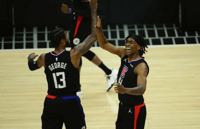 Jun 14, 2021; Los Angeles, California, USA; Los Angeles Clippers guard Terance Mann (14) reacts with guard Paul George (13) after scoring a basket and drawing a foul against the Utah Jazz during the first half in game four in the second round of the 2021 NBA Playoffs. at Staples Center.