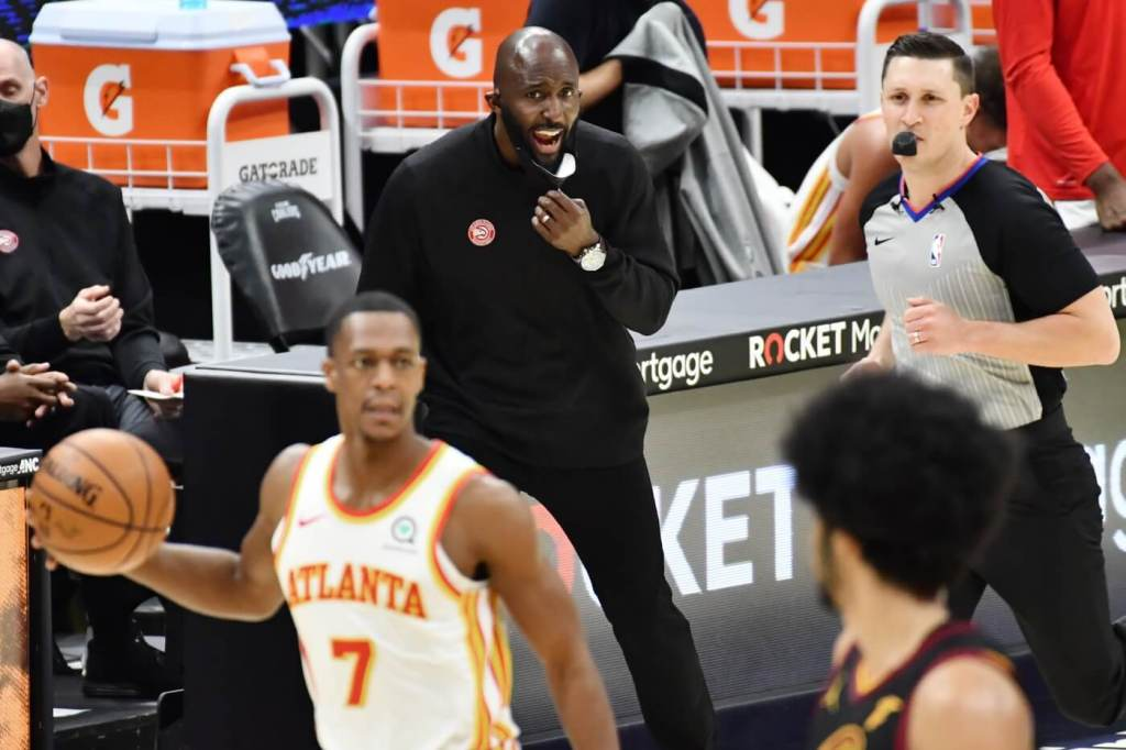 Feb 23, 2021; Cleveland, Ohio, USA; Atlanta Hawks head coach Lloyd Pierce yells to the team as guard Rajon Rondo (7) brings the ball up court during the third quarter against the Cleveland Cavaliers at Rocket Mortgage FieldHouse. Mandatory Credit: Ken Blaze-USA TODAY Sports