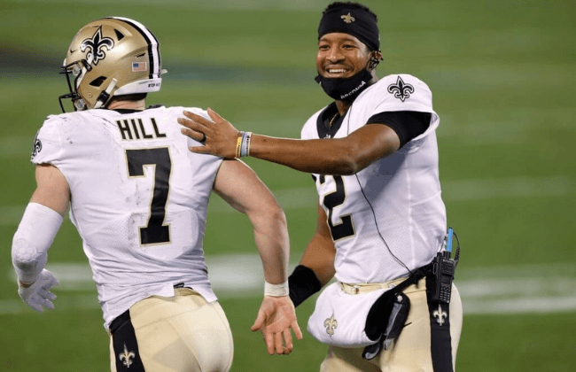 CHARLOTTE, NORTH CAROLINA - JANUARY 03: Quarterback Jameis Winston #2 of the New Orleans Saints shares a smile as he greets teammate quarterback Taysom Hill #7 during the second half of their game against the Carolina Panthers at Bank of America Stadium on January 03, 2021 in Charlotte, North Carolina. (Photo by Jared C. Tilton/Getty Images)