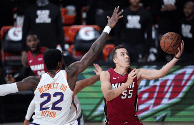 Aug 8, 2020; Lake Buena Vista, Florida, USA; Miami Heat's Duncan Robinson (55) goes to the basket as Phoenix Suns' Deandre Ayton (22) defends during the first half of an NBA basketball at Visa Athletic Center. Mandatory Credit: Ashley Landis/Pool Photo-USA TODAY Sports