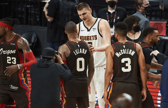 Jun 3, 2021; Portland, Oregon, USA; Denver Nuggets center Nikola Jokic (15) consoles Portland Trail Blazers guard Damian Lillard (0) after game six in the first round of the 2021 NBA Playoffs. at Moda Center. The Denver Nuggets won the game 126-115. Mandatory Credit: Troy Wayrynen-USA TODAY Sports