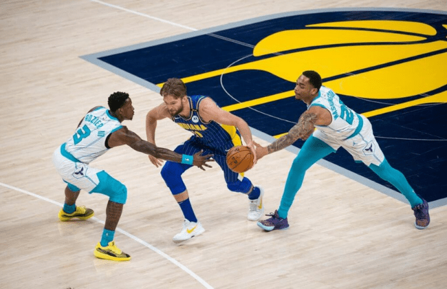 May 18, 2021; Indianapolis, Indiana, USA; Indiana Pacers forward Domantas Sabonis (11) dribbles the ball while Charlotte Hornets guard Terry Rozier (3) and forward P.J. Washington (25) defend in the first quarter at Bankers Life Fieldhouse. Mandatory Credit: Trevor Ruszkowski-USA TODAY Sports