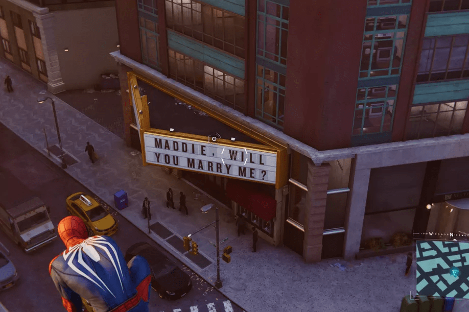"A screenshot from Marvel's Spider-Man showing Spider-Man crouched on a building. Below him is a theater marquee reading, ""MADDIE, WILL YOU MARRY ME?"" Marvel's Spider-Man, Insomniac Games, Sony Interactive Entertainment, 2018"