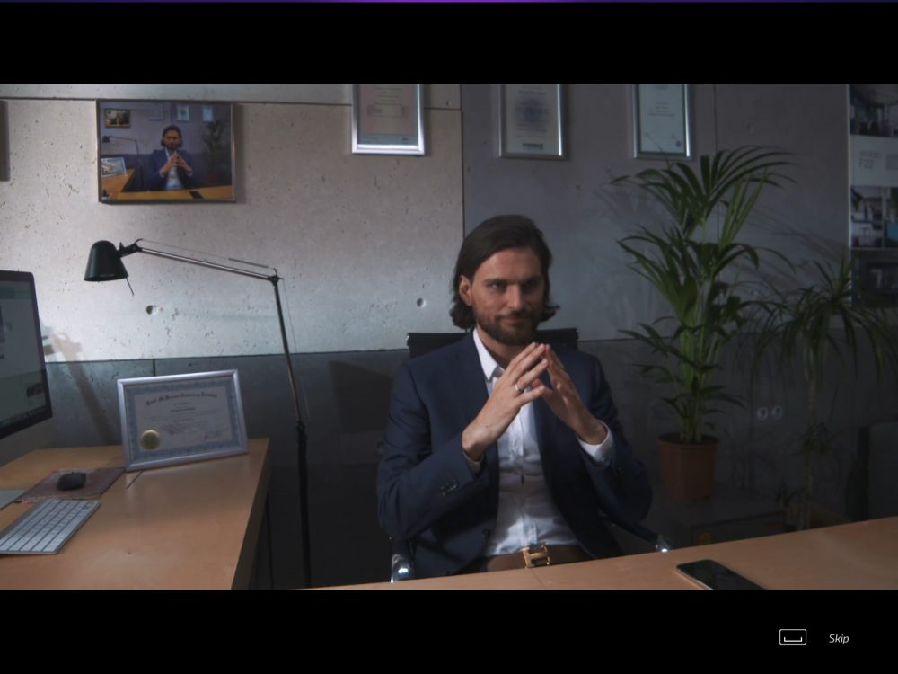 A man sits menacingly at an office desk with his fingertips touching together. Behind him, right, is a plant. Also behind him on the wall, left, is a framed photo that mirrors the exact same pose and room. Super Seducer 2, RLR Training Inc, Red Dahlia Interactive, 2018