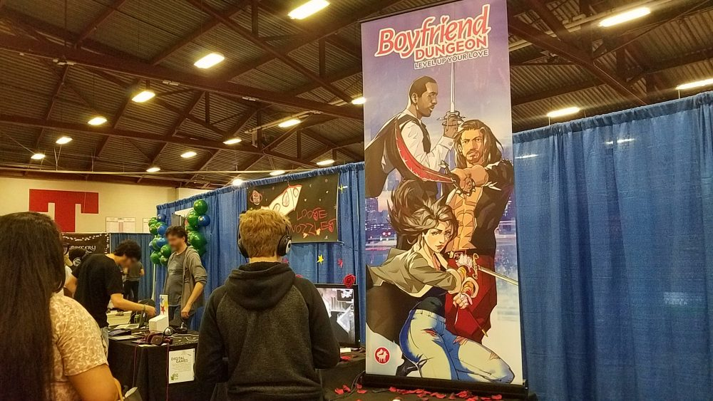 A photo of attendees in front of Boyfriend Dungeon's booth. The Boyfriend Dungeon Banner displays three of the game's possible love interests.