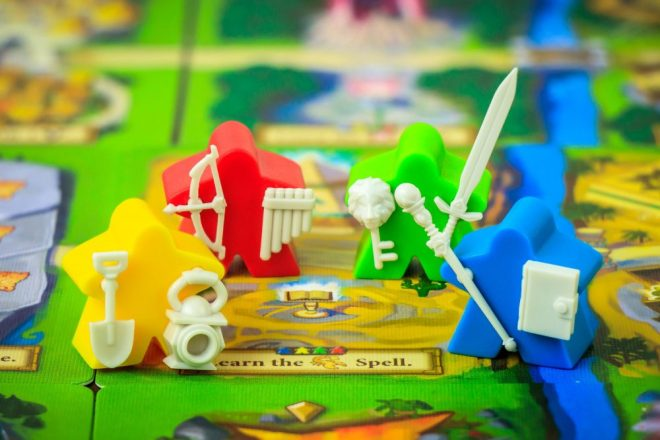 A photo of four Meeples. A yellow one holds a shovel and lantern, a red one holds a bow and arrow and set of flutes, a green one holds a sword and key with a lion on it, and a blue one holds a staff and book.