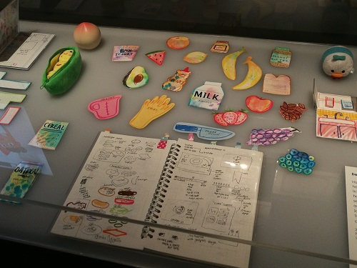 Display case containing a notebook with notes/sketches as well as hand-coloured, cut-out paper drawings of food items, Jenny Jiao Hsia