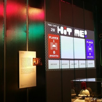 Hit Me! game (Kaho Abe, 2011) displayed on a screen; in the foreground in display cases are the hardhat controllers