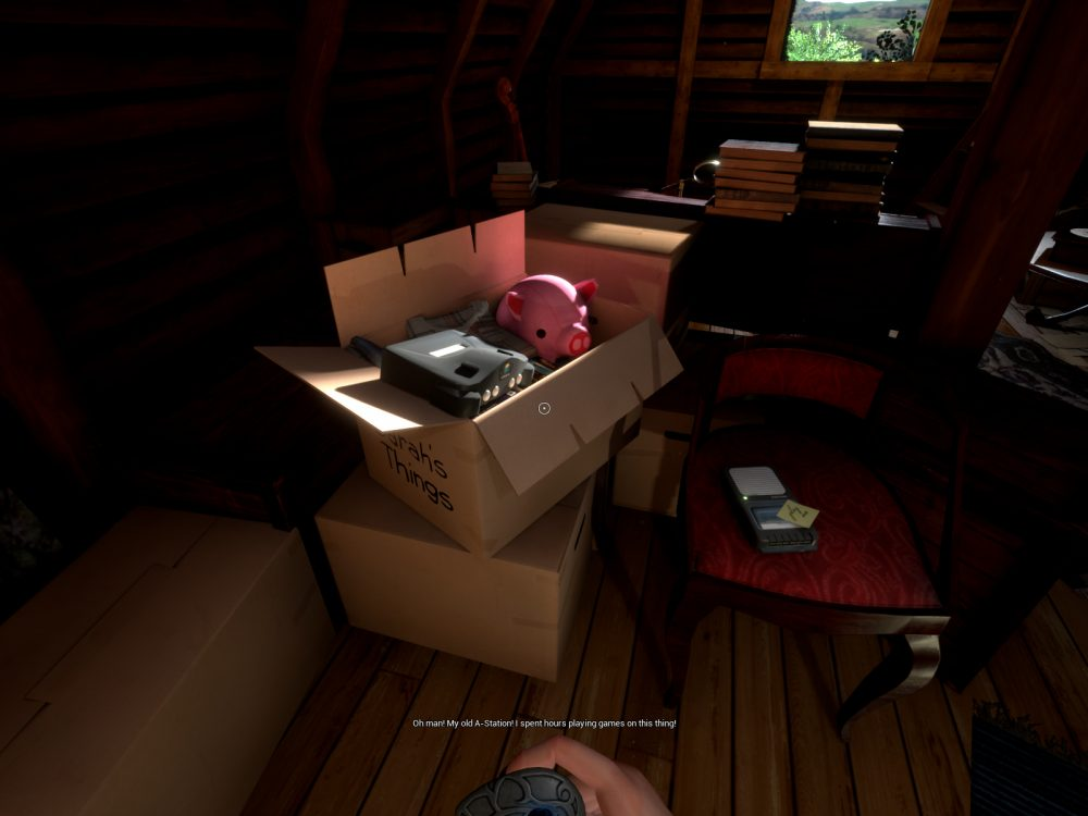 "A screenshot from What Never Was, showing a box labeled ""Sarah's Things"" containing a pink stuffed pig and a game console. The box is in a dimly lit attic, surrounded by piles of books, knick knacks, and other boxes. A caption reads, ""Oh man! My old A-Station. I spent hours playing games on this thing."""