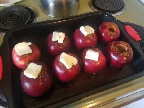 A photo of eight apples with butter and spices on top, ready to be put in the oven.