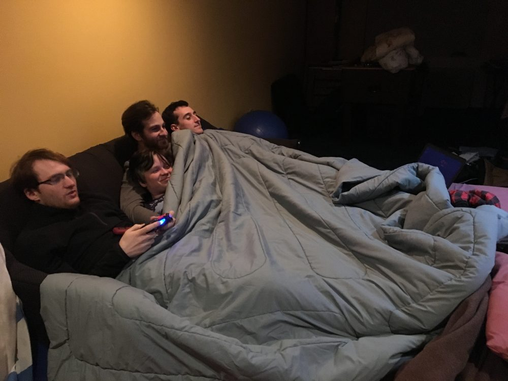 The photo from the featured image, of four adults, crowded extremely platonically into a pull-out couch in bed form. A gray comforter is pulled over all of them. The man on the far left holds the controller; the three people to the right have the blanket pulled up to their necks (it was COLD in that basement). The lighting is dim. Photo by author.