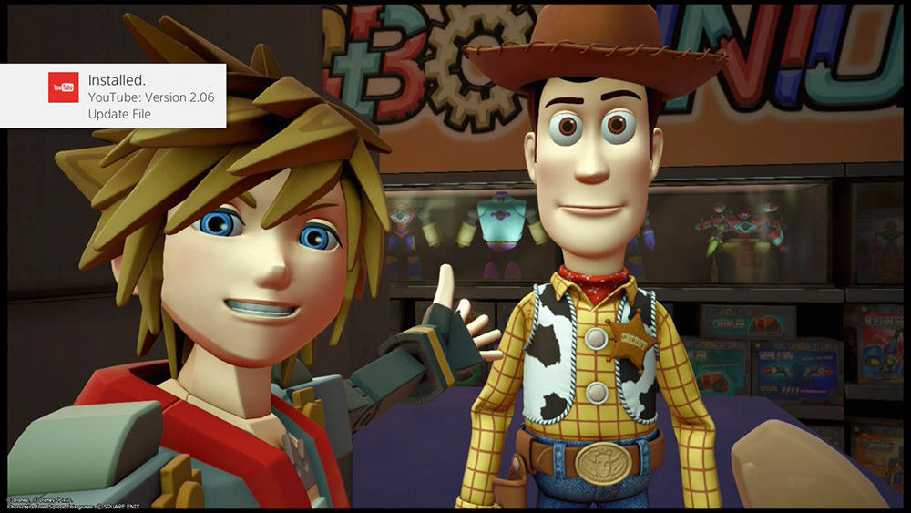 A selfie of Sora, grinning and gesturing to Woody, in front of a Toy Box banner. Woody stares vacantly into the camera. Kingdom Hearts III, Square Enix, 2019; Screenshot by... someone in the gang.