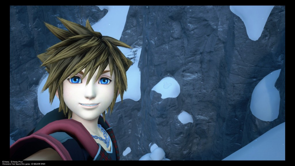 Sora takes a selfie in the snowy mountains of Arendelle. A Lucky Emblem is imprinted into the snow to the right of his head. Kingdom Hearts III, Square Enix, 2019.