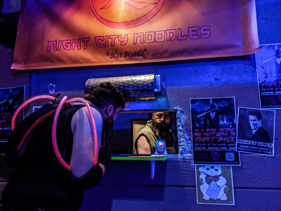 """A player crouches down to talk to the noodle vendor through the window of the noodle stand, which has a sign that reads """"Night City Noodles: Hot Noodz."""""""