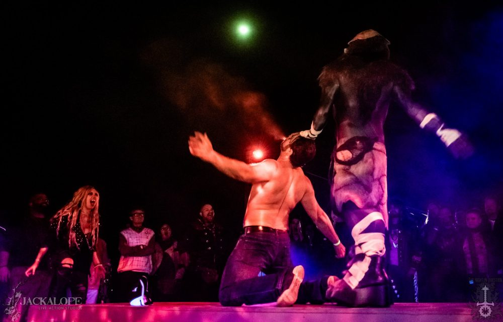 A costumed werewolf stands above a kneeling shirtless man, who is spitting out blood