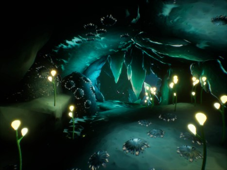 A cavern with plant-like structures glowing across its uneven surfaces. The image is all greens and blues, and the lights glow a soft yellow.