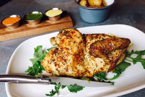 Half rotisserie chicken on plate with garnishes.
