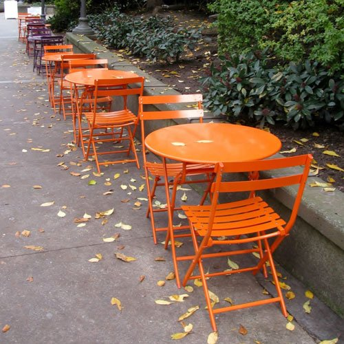 Row of tables and chairs outside.