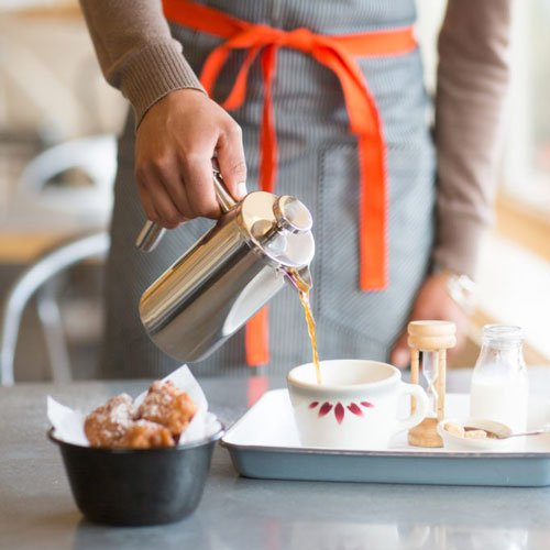 Order of apple fritters and server pouring coffee.