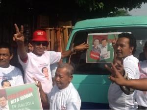 Ketua tim pemenangan Jokowi-JK Sidoarjo, Tito Pradopo (berkacamata)  bersama sopir memasang stiker Jokowi-JK