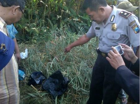 Kapolsek Tanggulangin Kompol Andi Yudianto melihat bungkusan yang berisi orok bayi.