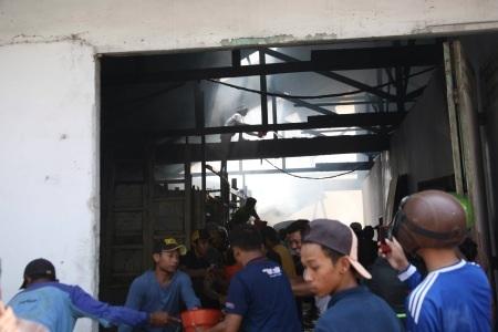 Petugas sedang memadamkan api yang melahap gudang bahan bangunan milik Johan