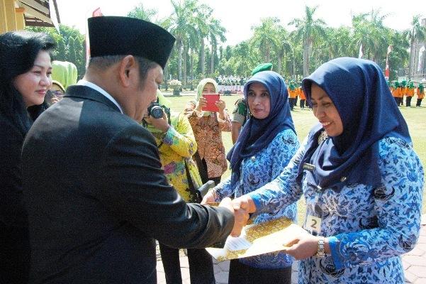 Foto : Bupati Sidoarjo, H. Saiful Ilah, SH, M. Hum disaksikan Kadinkes, Dr. Ika Harnasti menyetahkan Piagam Penghargaan kepada Anik Suaiba, di Alun Alun Sidoarjo. (foto humas pemkab/editor : kaji dar)