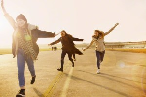 Teenage Girls Running with Arms Outstretched