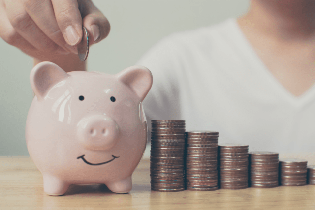 putting coins in a piggy bank for a budget
