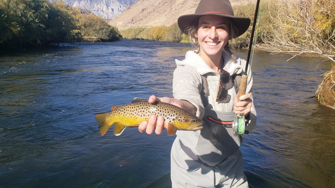 Young Girl holds up a Brown Trout while Fly Fishing on the Lower Owens River near Bishop California