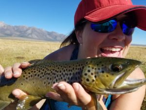 happy lady holds a good sized brown trout above the upper owens river