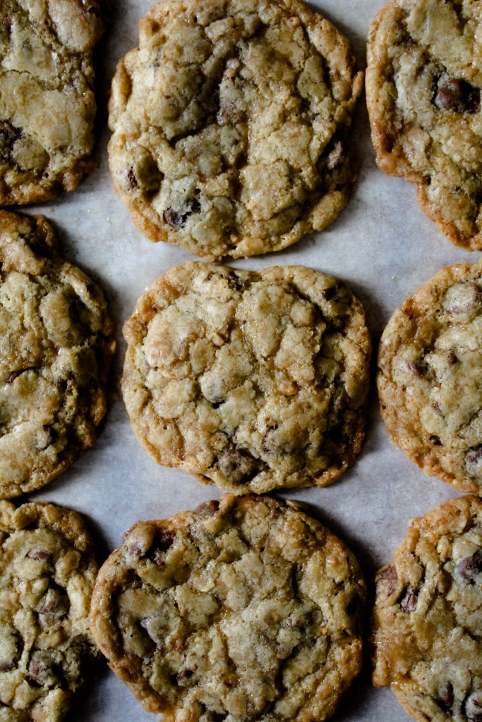 Chocolate chip and heath bar cookies lined on a tray.