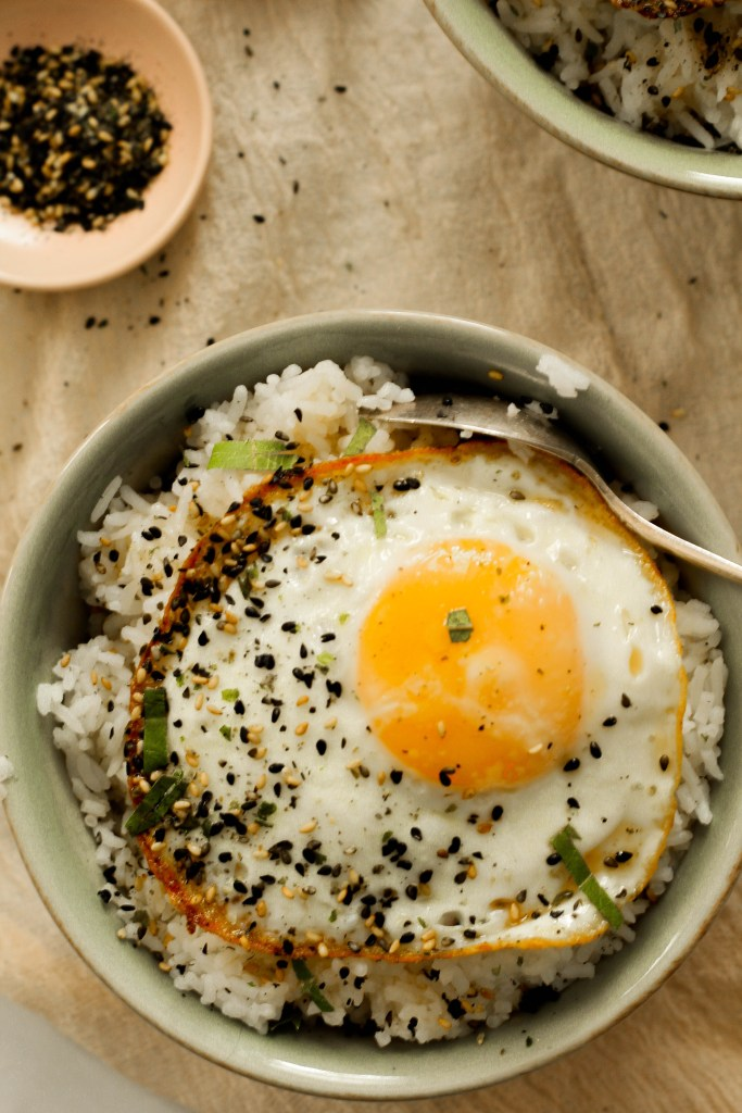 A green bowl sitting upon a biege cloth filled with rice covered in sesame sauce, a fried egg, and furikake.